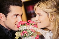 Close_up of a young couple looking at each other with a bouquet of flowers between them