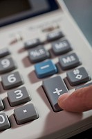 Close_up of a human finger pressing buttons of a calculator