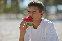 Close_up of a teenage boy eating a slice of watermelon