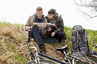 A couple sitting on a hill next to their bicycles looking at a map