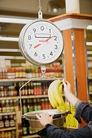 Man´s hand weighing a bunch of bananas on a weighing scale in a supermarket