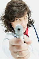 Portrait of a female doctor aiming with a handgun