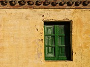 Yellow wall and green window of a traditional fishermen house Sa Riera Begur Costa Brava Baix Empordà Catalunya Spain