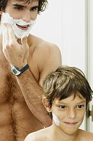 Reflection of a boy with his father applying shaving cream on their faces