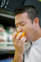 Close_up of a mid adult man tasting an orange