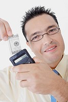 Portrait of a businessman holding a calculator and a dollar bill