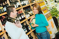 Close_up of a mid adult man and a young woman holding wine bottles in a supermarket