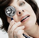 Portrait of a female doctor covering her eye with a stethoscope