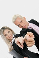 Portrait of a businesswoman and a businessman standing back to back and pointing