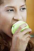 Close_up of a young woman eating an apple