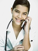 Portrait of a girl with a stethoscope around her neck and talking on a mobile phone