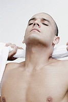 Close_up of a young man wiping his neck with a towel