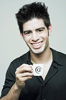 Portrait of a young man holding a cup of tea and smiling