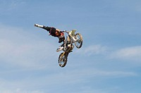 background motocross rider performing stunt air