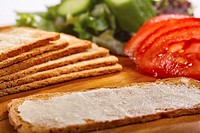 Slices of Melba toast, one buttered on a plate with fresh salad