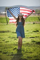 Beautiful cowgirl running with American flag in her arms