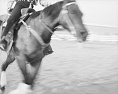 blurred galloping horse and rider