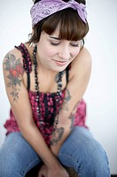 young woman with nose piercing and tattoos sitting down
