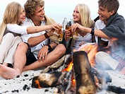 Young group of people sitting by bonfire at the beach drinking beer and having fun