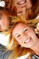 Three teenagers holding there heads together Picture taken from below