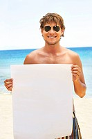A handsome man holding a billboard at the beach Ready to add your own text