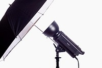 Monolight on stand with reflective umbrella used for photographic studio lighting  Isolated