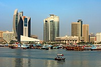 Dhow harbour at the Dubai Creek in front of modern high rising buildings of the National Bank of Dubai, the Chamber of Commerce and Industry and the D...