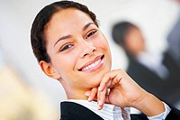 Young working female _ Beautiful portrait of a happy young woman smiling Sitting by her desk in an office, college or university environment with coll...