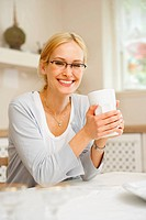 Portrait of a young successful woman, enjoying a cup of coffee in her home