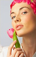 Fashion shot of a beautiful, professional model with pink flowers