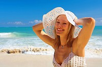 Photograph of a beautiful blonde standing by the sea in a white hat and summer dress