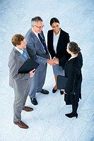 Handshake and teamwork A group of business people shaking hands in a light and modern office environment