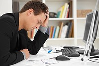 Side view of a stressed young man at office desk