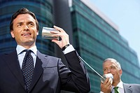 Two Businessmen with a tin can telephone