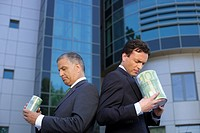 Two Businessman standing back to back with cylinders in their hands