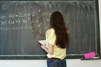 Female student writing formula at blackboard