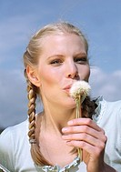 Young blond woman lying on meadow blowing dandelion seeds