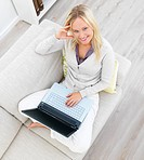 Happy Young woman sitting on sofa and using laptop