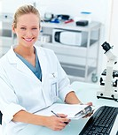 Happy young female researcher by microscope smiling