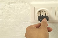 Woman putting plug into electrical outlet (thumbnail)