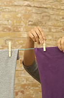 Woman hanging washing on clothesline (thumbnail)