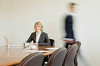 Businesswoman in conference room with person in background passing by, Munich, Bavaria, Germany