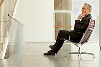 Businessman sitting on office chair in hall, Munich, Bavaria, Germany