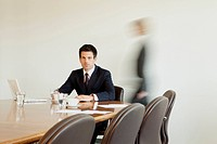 Businessman in conference room with person in background passing by, Munich, Bavaria, Germany