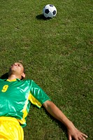 Exhausted Brazilian soccer player lying on grass