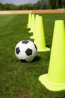 Soccer ball and pylons on grass