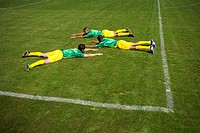 Outstretched Brazilian soccer players lying on grass