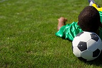 Brazilian soccer player lying on grass