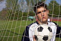 Soccer player holding a ball standing in goal