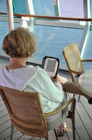 Cruise ship passenger reading an Amazon Kindle reader, Venice, Italy